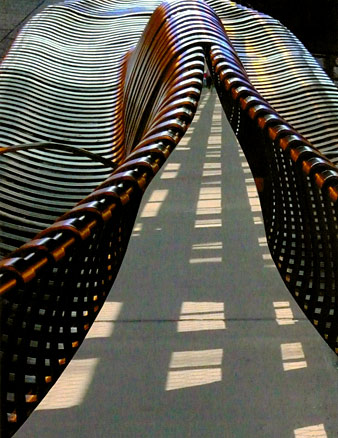 Two metal benches converge, their forms made of struts like zipper teeth, open onto a path with shadow stripes.