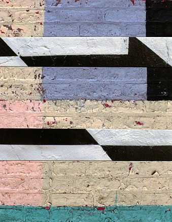 Black and white stripes interrupt blocks of pastel colors painted on brick