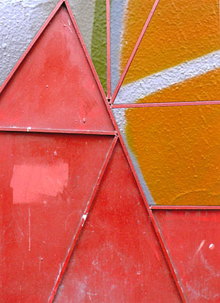 Irregular triangles of red metal door open to reveal graffiti of radiating lines, geometric composition